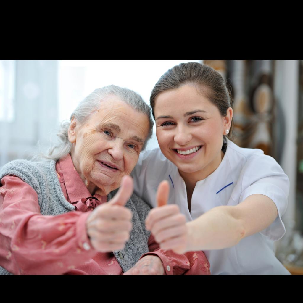 Seniorin und Pflegekraft haben Spaß